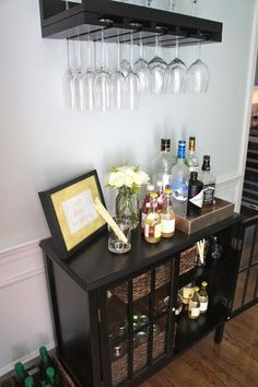 """I mentioned in this post that I'm using an empty wall in our dining room to create a small bar area. I used the Threshold Windham Accent Table from Target as my """"bar cart"""" and hung the Pottery Barn Holman Entertaining"""