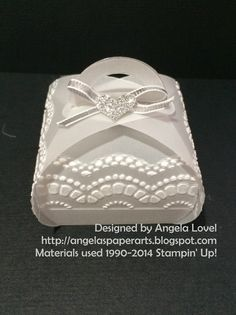 "Features the Stampin' Up! Curvy Keepsake Box thinlets die which can be purchased here: http://www3.stampinup.com/ECWeb/ProductDetails.aspx?productID=135853&dbwsdemoid=4011749 Also features other Stampin' Up products: Vellum, Delicate Designs embossing folder, silver 1/8"" ribbon, silver glitter paper, heart punch from the Itty Bitty Accents punch set. All available from my online store: http://www.angelaspaperarts.stampinup.net/"