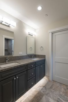 Underlit his and hers vanity with stone countertop and frameless mirrors. Recessed can lights above sink and shower area for even lighting perfect for aging in place.