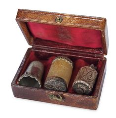 "EARLY 1800S SET OF THREE SEWING ACCESSORIES IN ORIGINAL LEATHER CASE 2.2"" (6 cm.) x 1 1/2"". 1"" thimble. A leather bound case with silk lining and having image of young girl on the cover contains three early silver sewing tools,namely a diminutive thimble,a thread-winter,and a tape measure with hand-inked silk tape. Circa 1800."