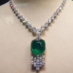 A spectacular Dehres Columbian Sugarloaf Cabochon Emerald weighing 75.57 carats suspended from an exquisite diamond necklace