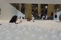 Wading pool filled with 1 million translucent polyethelene balls and a carpeted deck