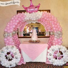 pink princess cake displayed inside a balloon princess carriage