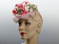 Vintage tilt hat 1940s summer fascinator trimmed in a profusion of gorgeous pink millinery flowers. The floral percher is secured by a velvet covered wire O-ring as seen in the 4th photo. The condition is very good with the exception of minor signs of vintage age to the millinery flowers. No stains on the flowers, but the green cloth leaves have faded. Some of the flowers have frayed edges that could be trim or turned under. All in all, a gorgeous hat and perfect for all your summer events…
