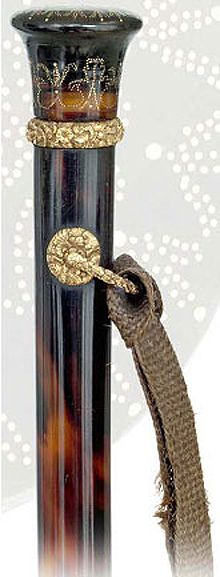 A first rate and early French dress cane entirely fashioned of tortoiseshell with a piqué-brodé knob and plain shaft with gold fittings. Decorated with miniscule gold pin-heads, the three quarter of an inch high knob's surface looks like micro lace and has its silky feel. The plain and elegantly tapering, solid tortoiseshell shaft, reflecting a superb, mottled warm color in a sublime translucency, is emphasized by a magnificently chased yellow gold collar with eyelets and swiveling bar .