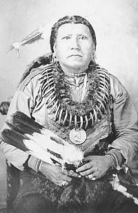 Pawnee Chief Boss Sun wearing bear claw necklace, peace medal, and holding feather fan. Late 19th century. Smithsonian Institution National Anthropological Archives.