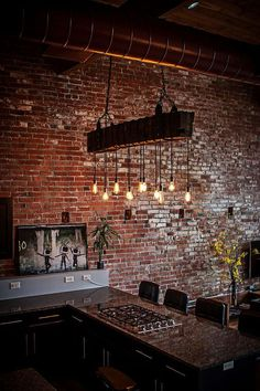 Exposed duct pipes, brick walls and lighting create a distinct modern industrial style in the kitchen