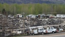 Electrical crews are seen working among burned-out buildings in the Beacon Hill neighbourhood of Fort McMurray, Alta., during a media tour of the fire-damaged Alberta city on Monday, May 9, 2016. (THE CANADIAN PRESS/Ryan Remiorz)