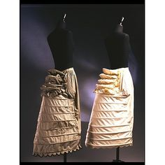 """1870 ... Crinolettes ... Britain ... Spring steel hoops, covered in striped cotton, fastened and adjusted with metal eyelets and tapes ... """"By 1865 the outline of the fashionable dress changed. The shape at the back of the body grew more exaggerated with a distinctive flattening at the front. Crinolettes, or half-crinolines, marked the mid-point between the cage crinoline and the bustle. They often had extra loops of steel, which acted as a bustle."""" ... at V-A Museum"""