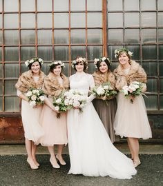 Bridesmaids in blush dresses with faux fur wraps
