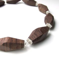 This handmade necklace is made up of 10 facetted element made out of wenge wood, connected through matt silver endpieces. The necklace comes with an invisible magnetic lock.