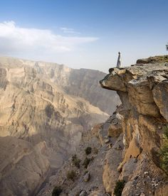 Guide Kareem inspects Wadi Ghul the so-called 'Grand Canyon of Arabia' from the top of Jebel Shams the highest peak in Oman's Hajar Mountains // photo by Justin Foulkes #oman #gulf #mountain by lonelyplanettraveller