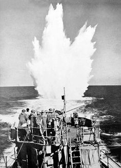 A depth charge attack under way in the Atlantic, as seen from one of the destroyers supplied to Britain by the USA.