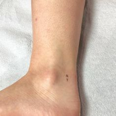 NY tattoo on the ankle.
