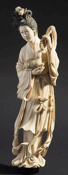 A Japanese carved ivory okimono: of a woman in traditional robes feeding a lamb, unsigned, 35cm. high. with lamb.