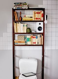 A picture of a multimedia centre on shelves above a toilet