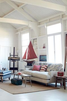 A white interior with a nautical decorating theme. Love the off white sofa and the striped armchair with accents of blue and red here and there. Image by DFS Furniture.