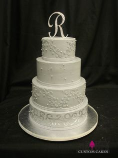 Gray buttercream base with gray fondant ribbons at base of tiers with hand painted silver details on bottom tier. Chantilly lace on third and top tier and edible dragees on second tier.