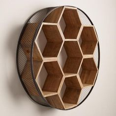 Encircled by a metal and chicken wire frame, our round wall unit houses a honeycomb of hexagonal wooden cubbies, lending a warm, homey feel to your space.