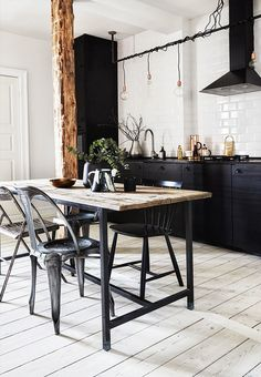 Black kitchen units | black kitchen cupboards | pale wood floors in the kitchen | trestle table with black legs