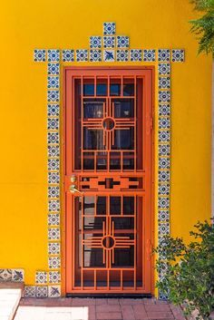 Colorful orange door with spanish tile surround. In New Mexico
