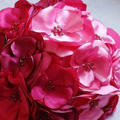 Mooie alternatieve boeket beschikt satijn bloemen in verschillende tinten van magenta, Felroze en flamingo een prachtige ombre-effect te creëren. Het handvat is omwikkeld met wijn satijn lint te voltooien de arcering. Elke bloem is zorgvuldig handgemaakte en elk heeft een spreiding
