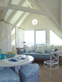White makes every room look bigger – especially this lofted attic space with a soaring ceiling – because it allows light to reflect. A wooden daybed nestles up to a row of windows, and the coastal color palette and woven carpeting keep the look feeling fresh and effortless.(I would want something to cover the windows when needed, but I love the feel of the room.)