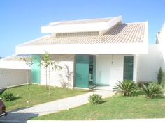 Em um terreno em declive, moradia de casal jovem com dois filhos pequenos.: Casas tropicais por Solange Figueiredo - ALLS Arquitetura e engenharia