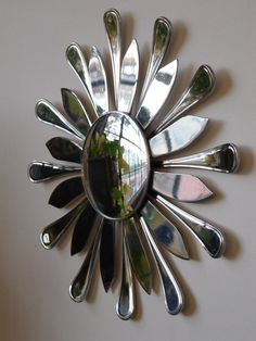 """Made from stainless steel butter knives. In this one, the artist used both the handles and the knives themselves to form alternating rays. 11"""" across, including a 3.75"""" convex mirror."""