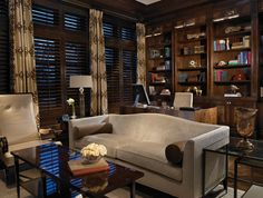 The heavy wooden desk and bookshelf in this home office are contrasted by light neutral furniture and glass tables.