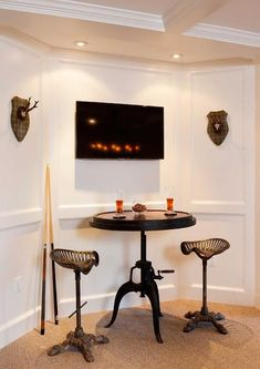 Basement man cave boasts a coffered ceiling over paneled walls lined with a flatscreen TV over an ...