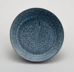 Ru stoneware dish. The body of the dish is stained bluish-black where exposed and has opaque lavender blue glaze with close crackle. There are three elliptical spur marks and an incised character on the base, which is glazed, as is the foot.