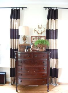 striped drapes, dresser, antlers, plant in urn on top of charger plate