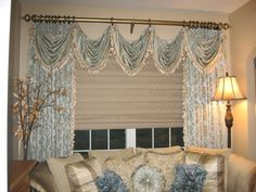 Stationary Drapery Panels with Swag Overlays on Decorative Wood Poles