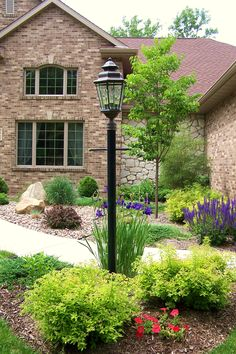 Gorgeous curb appeal and entryway design using shrubs, flowers, and trees.