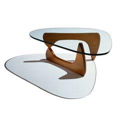 Isamu Noguchi, 1944 - Coffe table    Noguchi lui-même considérait la Coffee Table comme sa création de mobilier la plus réussie, notamment parce qu'elle rappelle beaucoup les sculptures en bronze et marbre qu'il créait à l'époque et qu'elle transpose de manière authentique les éléments biomorphiques de leur langage formel dans un meuble à l'esthétique sculpturale. Un lourd plateau de verre d'épaisseur repose sur deux pieds identiques disposés à angle droit.