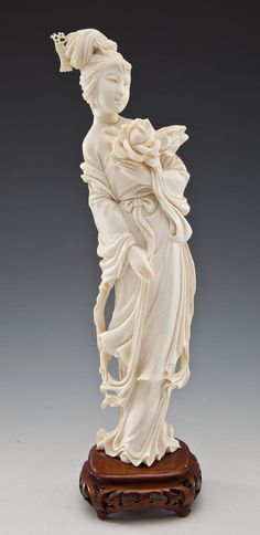 """DESCRIPTION: Carved ivory figure of a woman with flower, attached to carved wooden base. MEASUREMENTS: 11"""" tall. CONDITION: Minor wear as expected with handling. IMPORTANT NOTE: Pre-ban and African in origin. From a Pennsylvania estate and acquired during the 1950's to 1980's. Documentation available to the winning bidder upon request. Cannot be shipped out of the United State or to California, New Jersey, or New York. See Auction Terms & Conditions."""
