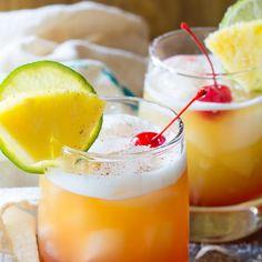 Drunken Monkey Cocktail - a vibrant fruity tiki drink. Ingredients: 6 ounces orange-pineapple juice blend 3 ounces coconut rum 1 ounce spiced rum dashes bitters Fresh ground nutmeg Maraschino cherries in juices Lime slices Fresh pineapple wedges Fruity Drinks, Smoothie Drinks, Refreshing Drinks, Summer Drinks, Alcoholic Drinks, Spiced Rum Drinks, Smoothies, Bar Drinks, Cocktail Drinks