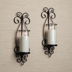 "Add a touch of distinction to your rooms decor with Danya B™ San Remo Wall Sconce Set.  A beautiful extension of black twisted wrought iron, these sconces have a cylindrical  glass hurricane suitable for pillar candles. Candles not included. 26.5"" high."