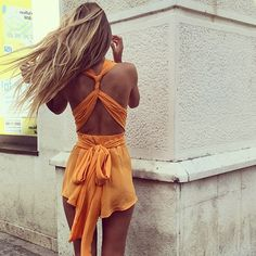 This romper is perfect for summer outings. the color makes the models tan look superb! And all the different strings of fabric wrapping around her back look really cute
