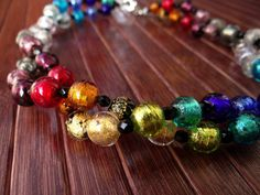 """Elena In this necklace the Murano glass beads are created using gold or silver leaf """"submerged"""", that is melted in the core of the bead itself. A double thread of multicolor beads alternated with black crystals create an elegant and young-looking effect, an accessory suited both for day and night, in any season."""