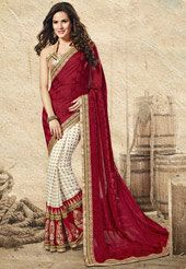 Definitely you will look bodacious and bedazzle your folks in any big fat party. Cast a chic charm when you step-in this, opulent and exquisite dark red and off white faux crepe jacquard and faux georgette jacquard half and half saree designed with zari, dori, stone, lace and patch border work. As shown, light copper brocadeblouse fabric is available and the same can be customized in your style or pattern; subject to fabric limitation. (Slight variation in color, jacquard, brocade design…