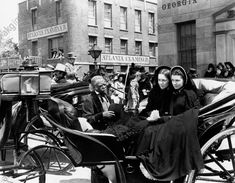 akg-images -Actresses Vivien Leigh (right) and Olivia De Havilland, as Scarlett O'Hara and Melanie Hamilton respectively in Gone with the Wind by Victor Fleming, are sitting on a carriage dressed in dark colours. United States, 1939.