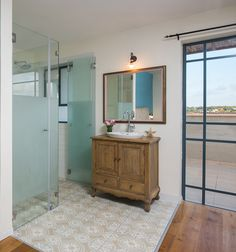 An open bathroom with glass-walled toilets and shower, for a master bedroom. By Liat Hadas, Architecture & Design.