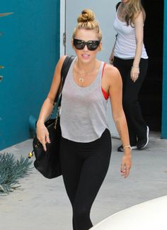 Miley demonstrates the perfect yoga topknot. #mileycyrus #hair