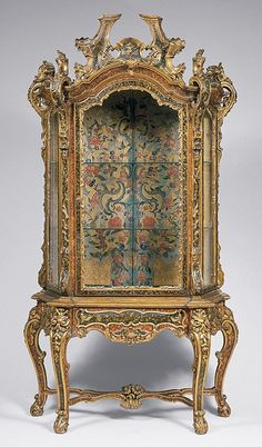 Rococo cabinet. The heavy embellishment and gold, almost over the top in pattern and