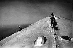 Men repairing storm damage to Graf Zeppelin while flying over the Atlantic Ocean, 1934.