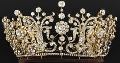 Poltimore Tiara, originally made by Garrard for Florence, Lady Poltimore, wife of the second Baron Poltimore, in the 1870s, of diamonds set in gold and silver. Clusters of cushion-shaped and old-cut diamonds are set amongst scroll motifs topped with more diamonds. It is a convertible piece, breaking down into a necklace and a set of 11 brooches. Bought in 1959 for Princess Margaret, who wore it at her wedding.