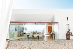 Floor to ceiling glass walls in dining space with modern furniture, and the exterior is all stone