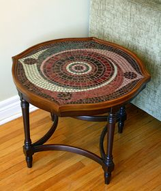 """wow!! $900 This small vintage table of an unusual curvilinear shape was given a second chance with mosaic, custom-tailored to the table's individual features. Complementing the table's graceful lines and rich brown tones, the design features circular and spiral motifs in gold-grained and plain glass tiles in shades of emerald, pale green, wine red, mahogany and bronze.The grout of the mosaic has been sealed to protect it. Measurements: - table top: 21"""" x 21"""" table height: 17"""" weight:10 lb"""